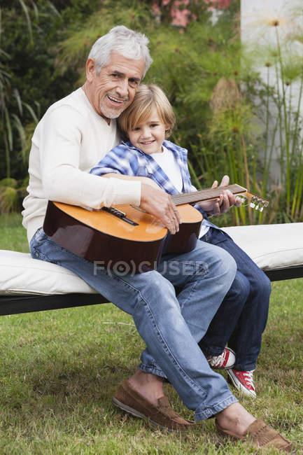 Abuelo y nieto con guitarra en el banco al aire libre - foto de stock