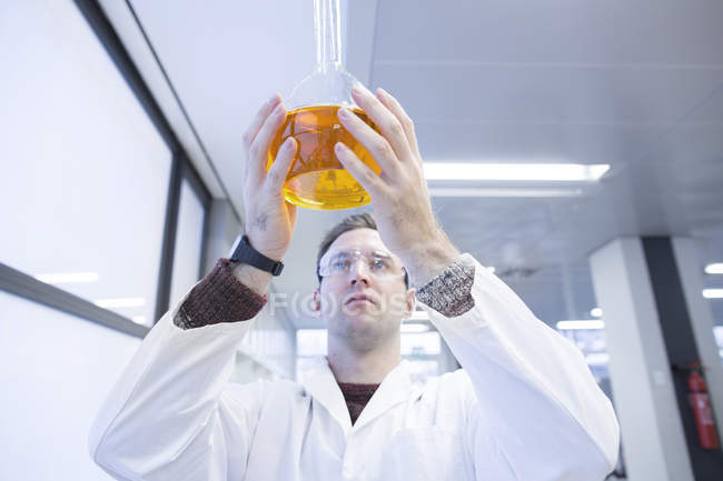 Chemist holding round bottom flask in lab — Stock Photo
