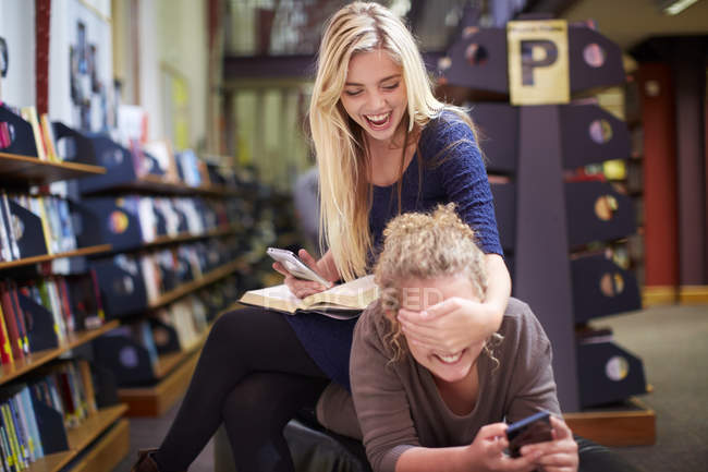 Two playful female students in a library — Stock Photo