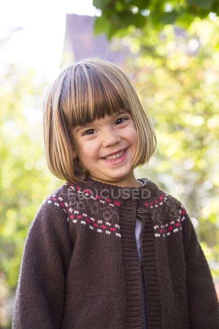Portrait of smiling little girl wearing brown cardigan — Stock Photo
