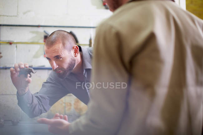 Two men in a sculptor's workshop looking at animal figurine — Stock Photo