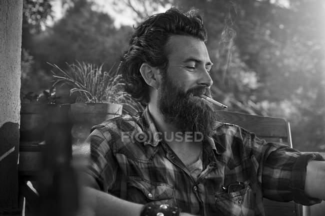 Человек с бородой курит сигарету на крыльце — стоковое фото