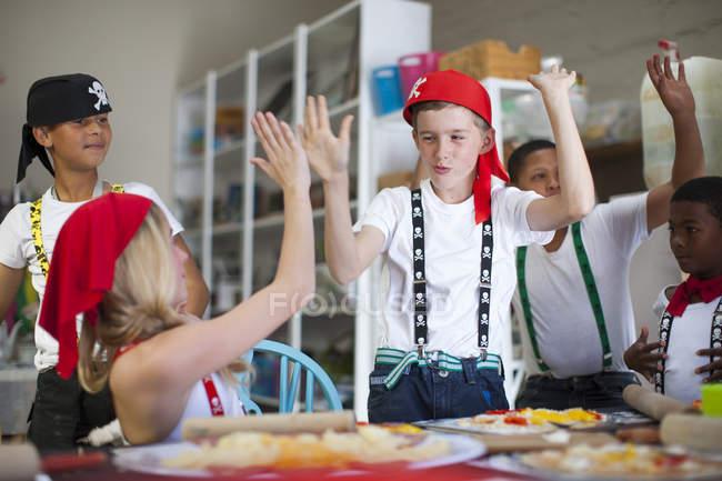 Kinder, verkleidet als Piraten Spaß auf einer Party am Tisch mit pizza — Stockfoto