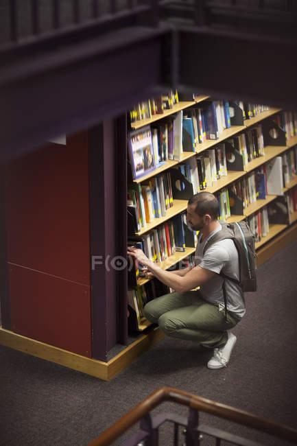 Студент в библиотеке берет книгу с книжной полки — стоковое фото