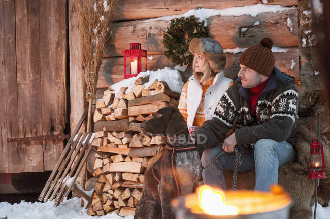 Couple avec chien à la cabane en bois dans la neige — Photo de stock