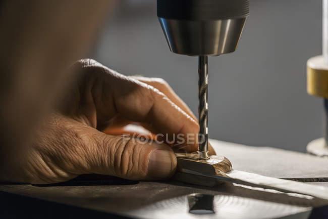 Knife maker in workshop at work drilling — Stock Photo