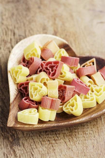 Heart shaped pasta on a wooden heart shaped plate — Stock Photo