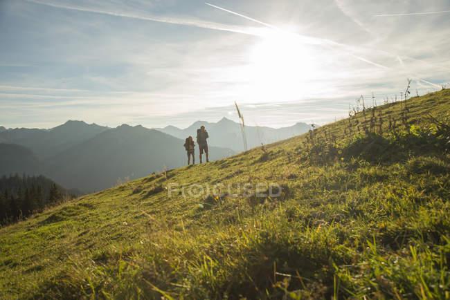 Austria, Tyrol, Tannheimer Tal, young couple hiking on alpine meadow — Stock Photo