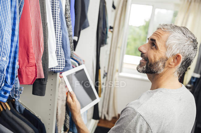 Man with his digital tablet standing at his walk-in closet — Stock Photo