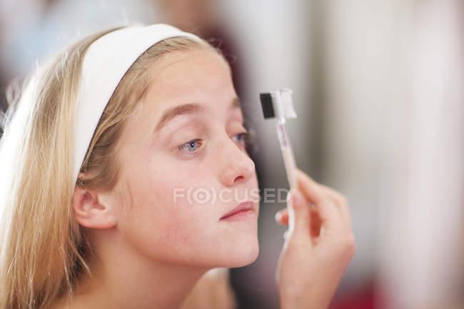 Girl on a beauty farm applying make-up — Stock Photo