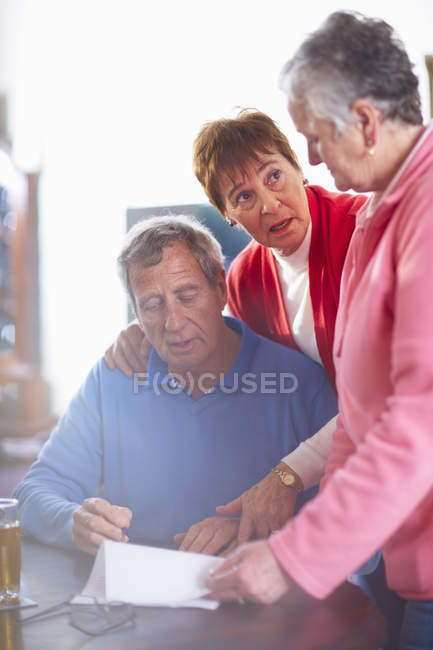 Three senior people with document — Stock Photo