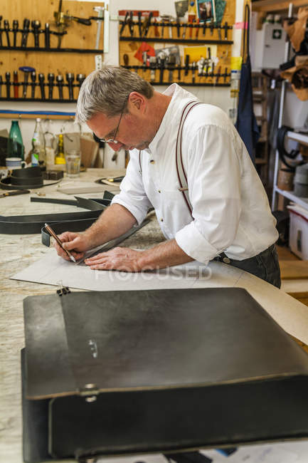 Saddler preparing stencil for rucksack — Stock Photo