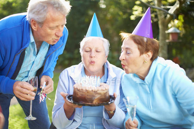 Senior woman blowing out candles on birthday cake — Stock Photo