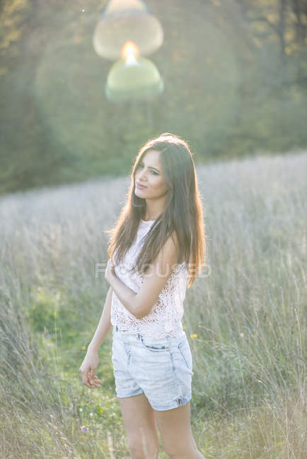 Portrait of young woman standing on a meadow in backlight — Stock Photo