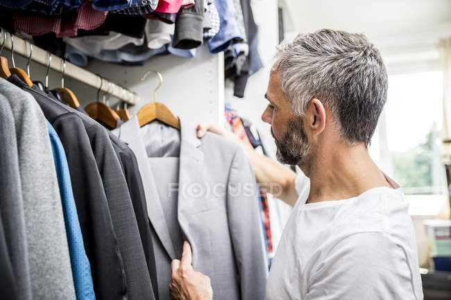 Man choosing clothes at his walk-in closet — Stock Photo
