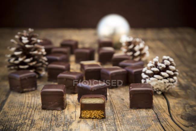 Caramelos de chocolate enteras y en rodajas con piñas de abeto en la madera - foto de stock