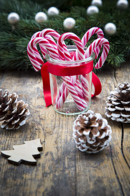 Glass of sugar canes and fir cones on wood — Stock Photo