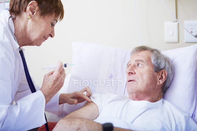Doctor injecting senior man in hospital bed — Stock Photo
