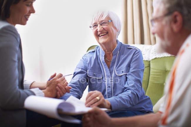 Sonriendo pareja mayor y mujer con documento - foto de stock