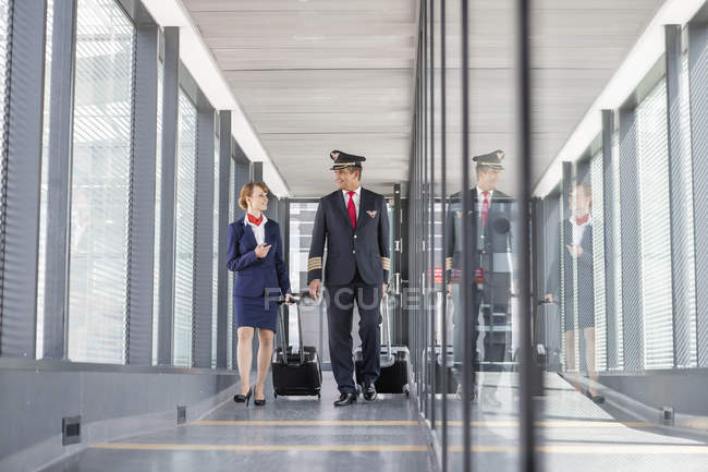 Piloto y azafata en el pasillo del aeropuerto - foto de stock