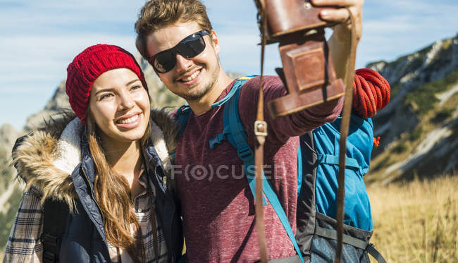 Austria, Tyrol, Tannheimer Tal, young couple taking self portrait with old-fashioned camera — Stock Photo