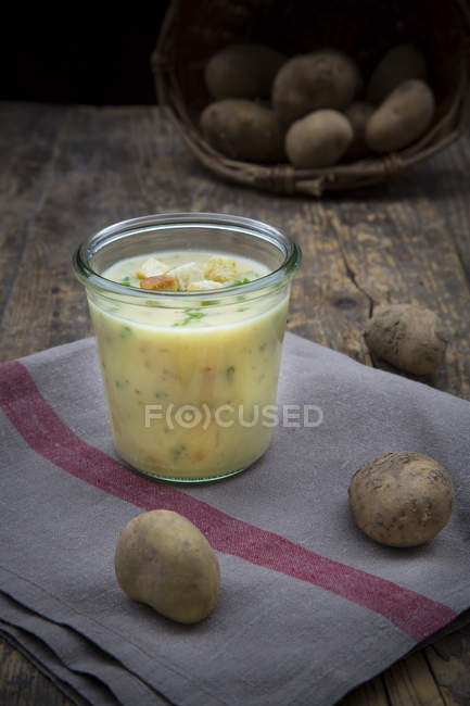 Скло картопляний суп гарнір з цибулею і грінками на кухонне рушник і дерева — стокове фото