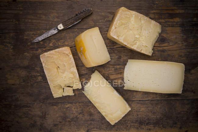 Различные куски сыра коровьего молока Венето и карманный нож на темной древесины — стоковое фото