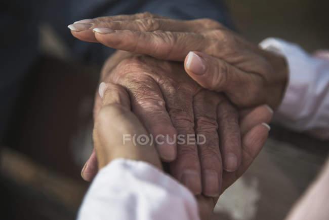 Fille tenant la main d'un homme âgé — Photo de stock