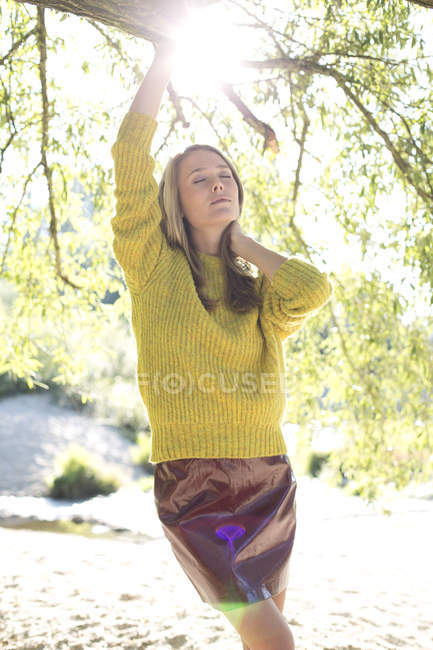 Young woman wearing knit pullover and mini skirt relaxing in nature — Stock Photo