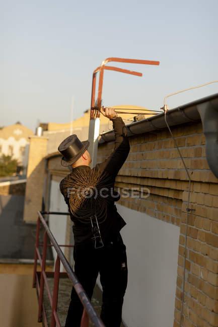Spazzacamino che lavora sul tetto dell'edificio — Foto stock