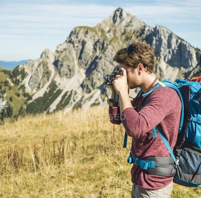 Austria, Tirolo, Tannheimer Tal, giovane uomo che scatta foto sul prato alpino — Foto stock
