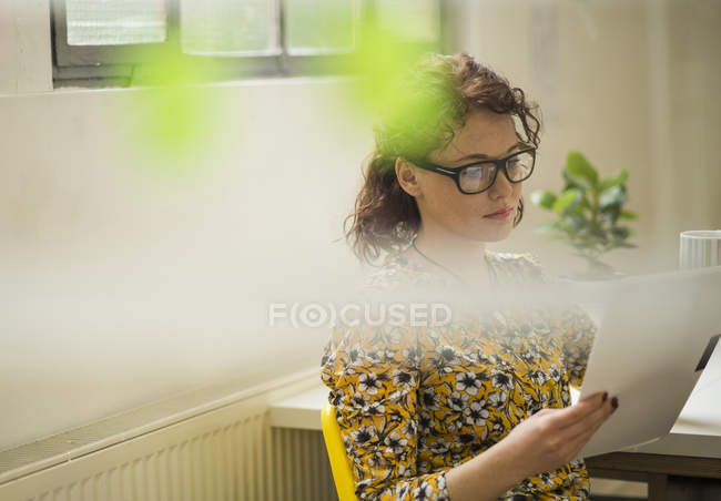 Young businesswoman reading document in office — Stock Photo