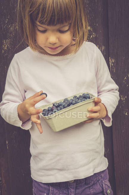 Cropped portrait of little girl with box of blueberries — Stock Photo