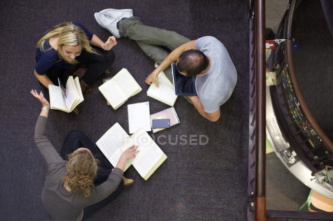 Three students learning in a library — Stock Photo
