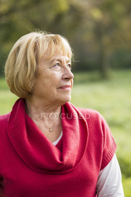 Portrait of blond senior woman wearing red pullover — Stock Photo