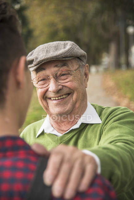 Крупным планом улыбающегося пожилого человека, кладущего руку на плечо внука — стоковое фото
