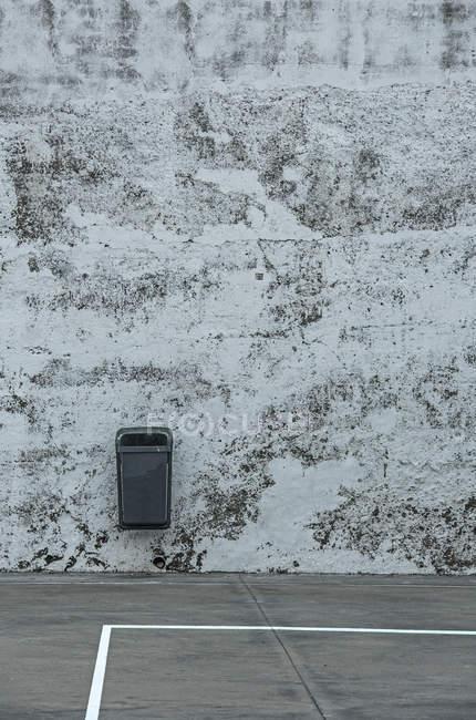 Depósito de residuos colgado en la pared en la esquina de un campo de deportes - foto de stock