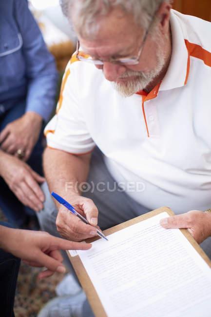 Hombre mayor firmando documento - foto de stock