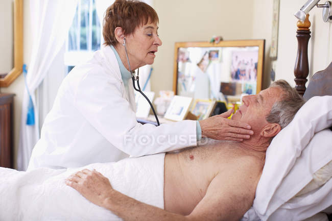 Médico a examinador senior hombre en casa - foto de stock