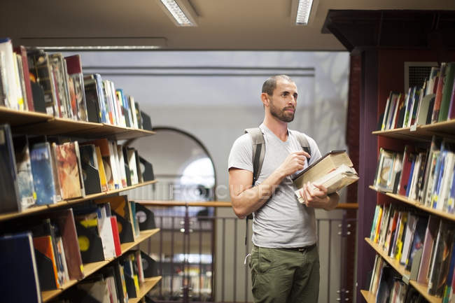 Student in einer Bibliothek im Bücherregal — Stockfoto