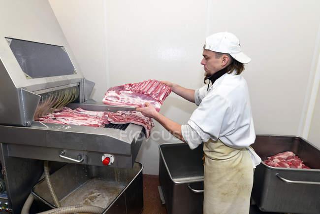 Людиною покласти нарізку м'яса в маринування машини в муніципалітет бійня — стокове фото