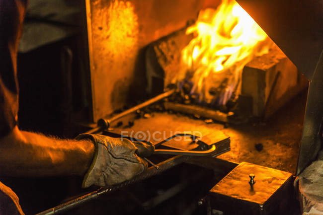 Knife maker in workshop heating workpiece — Stock Photo
