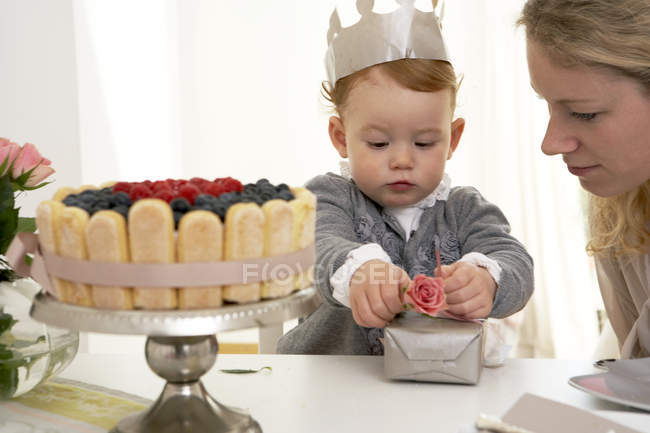 Дівчинка у короні розпакування присутній на перший день народження — стокове фото