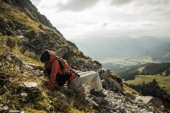 Österreich, Tirol, Tannheimer Tal, junge weibliche Wanderer erholend in Bergen — Stockfoto