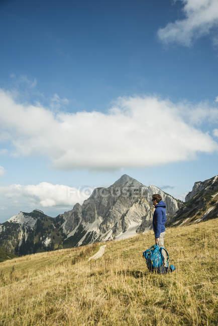 Austria, Tirolo, Tannheimer Tal, escursionista con zaino sul prato alpino — Foto stock