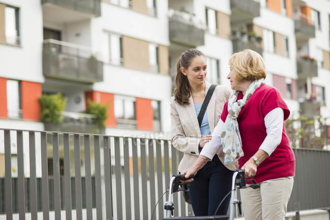 Granddaughter assisting her grandmother walking with wheeled walker — Stock Photo