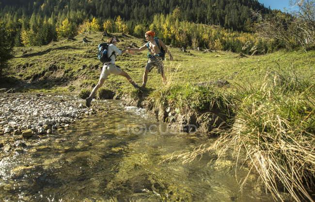 Áustria, Tirol, Tannheimer Tal, dois jovens caminhantes que atravessam a água — Fotografia de Stock