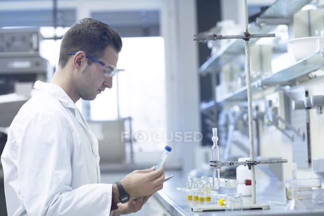 Chimiste travaillant en laboratoire avec le tube à essai — Photo de stock