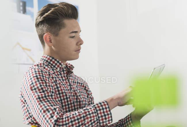 Junger Mann im Büro mit digitalem Tablet — Stockfoto