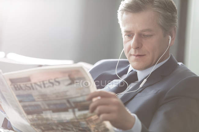 Businessman with earbuds reading newspaper at the airport — Stock Photo